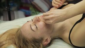 Blonde woman doing self-massage, facial massage lying in bed at home stock footage