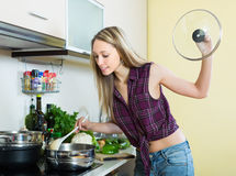 Blonde woman in domestic kitchen Stock Photo