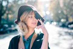 Blonde woman dreaming in hat closeaup fashion outdoors lifestyle. Young girl model portrait look on the street of Rome in coat white hair Royalty Free Stock Image