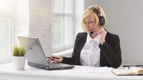 The Customers Help Line. Blonde woman dressed in black jacket and white shirt working as customer call center operator, help line on laptop via headset in white stock video footage