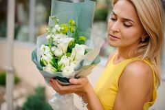 Blonde woman dressed in a yellow dress holding a white and green bouquet of flowers. With closed eyes on the blurred outdoors background Royalty Free Stock Photography