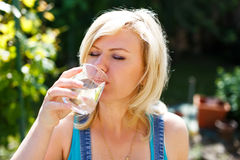 Blonde woman drink water outdoor Stock Image