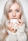 Blonde woman drinking a cap of tea Stock Photography