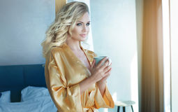 Blonde woman drinking coffee. Stock Photos