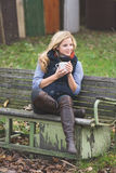 Blonde woman drinking outdoors Stock Images