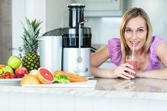 Blonde woman drinking a smoothie in the kitchen stock photography