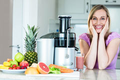 Blonde woman drinking a smoothie in the kitchen royalty free stock photos