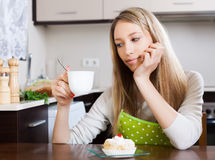 Blonde woman drinking tea with cake at table Stock Image