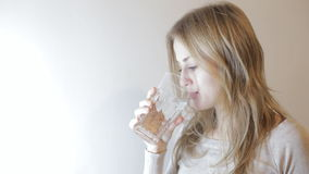 Blonde woman drinking water. Blonde young woman drinking a glass of water stock footage