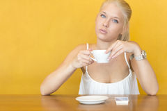 Blonde woman drinks coffee at cafe Royalty Free Stock Image