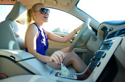 Blonde woman driving. Blonde woman with sunglasses driving the car stock photos
