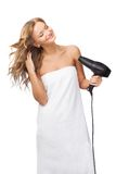 Blonde woman drying her hair. Happy blonde woman drying her hair over white background Stock Photo