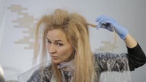 Blonde woman dyes her hair herself. Coloring hair at home. Blonde woman dyes her hair herself. Coloring hair at home stock footage