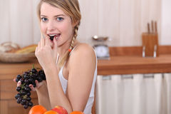 Blonde woman eating grapes Royalty Free Stock Photos