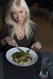 Blonde woman eating salad for lunch. Blonde woman sitting at cafe eating salad for lunch with a glass of water stock images