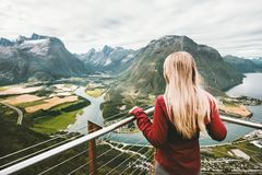 Blonde woman enjoying mountains landscape. Travel Lifestyle adventure vacations success emotions in Norway girl standing alone on Rampestreken viewpoint stock photos