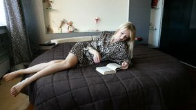 Blonde woman enjoying reading a book in bedroom lying on round bed smiling in pleasure in leopard dressing gown. Pretty young blonde woman enjoying reading a stock footage
