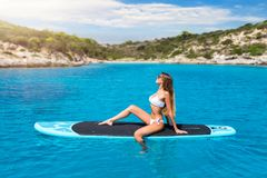 Blonde woman enjoys a hot summer day on a surfboard stock image