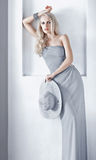 Blonde woman in evening dress. Elegant blonde in evening dress, with hat in hand Royalty Free Stock Images