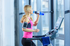 Blonde woman exercising on treadmill and drinking water Stock Image