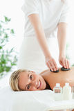 Blonde woman experiencing a stone therapy. In a wellness center Stock Image