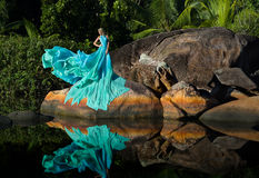 Blonde woman in extreme long dress on rocks of Seychelles Stock Images