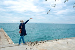 Blonde woman feeding seagulls in cloudy autumn day Stock Photography