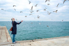 Blonde woman feeding seagulls in cloudy autumn day Stock Images