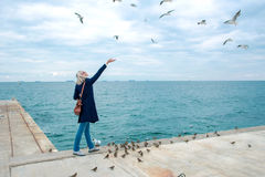 Blonde woman feeding seagulls in cloudy autumn day Royalty Free Stock Images