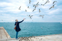 Blonde woman feeding seagulls in cloudy autumn day Royalty Free Stock Photography