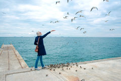 Blonde woman feeding seagulls in cloudy autumn day Royalty Free Stock Photo