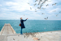 Blonde woman feeding seagulls in cloudy autumn day Royalty Free Stock Photos