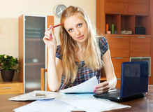 Blonde woman with financial document and laptop Stock Photo