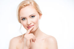 Blonde woman with finger on lip smiling at camera, body care concept. Attractive blonde woman with finger on lip smiling at camera, body care concept Royalty Free Stock Images