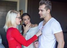 Blonde woman flirting with disloyal man, girlfriend in shock royalty free stock photo