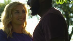 Blonde woman flirting with her african-american man, couple watching in camera. Stock footage stock video