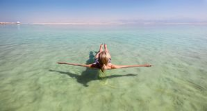 Blonde woman floating in the turquoise waters of the Dead Sea. Panoramic view of a blonde woman floating weightless in the turquoise waters of the Dead Sea stock photography