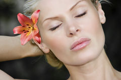 Blonde womans face with flower. Blonde Hawaiian island woman relaxing in a Maui park with a flower behind her right ear Royalty Free Stock Photos