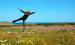 Blonde woman in the flower field. Playful blonde woman in the field full of flowers stock photo