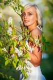 Blonde woman in a flowered garden Stock Image