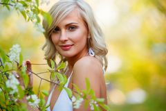 Blonde woman in a flowered garden Royalty Free Stock Photography