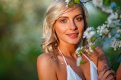Blonde woman in a flowered garden Stock Photos