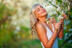 Blonde woman in a flowered garden Stock Images
