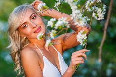 Blonde woman in a flowered garden Royalty Free Stock Photo