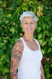 Woman with flowered tattoos on her arm. Blonde woman with flowered tattoos on her arm stock photo