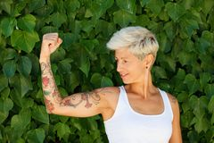Woman with flowered tattoos on her arm. Blonde woman with flowered tattoos on her arm stock photography