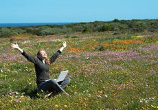 Blonde woman in the flowers. Blonde woman in casual clothes sitting with her laptop  in the field of flowers Royalty Free Stock Photos