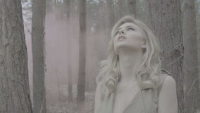 Blonde woman in the forest. Trying to escape with the smoke behind stock footage