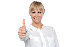 Blonde woman in formal attire showing thumbs up gesture Stock Photography