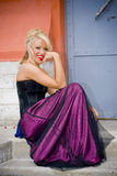 Blonde woman in formal gown. A young blonde woman in a purple and black formal gown Royalty Free Stock Images